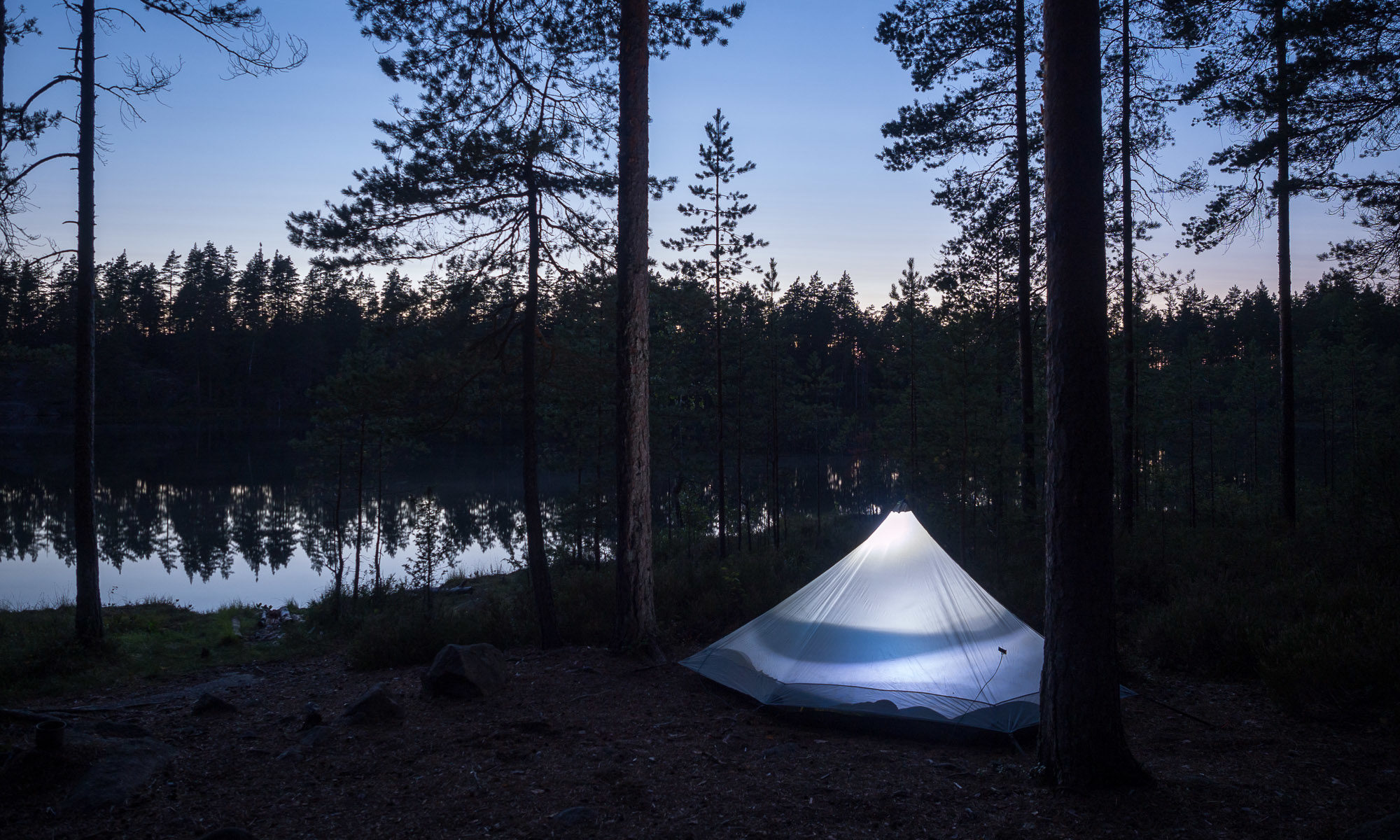 Nuuksio National Park in summer. Camping with a tent, nights are getting darker in August. Nature near Helsinki, Finland.